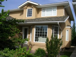 A recently painted home with stucco siding and newly installed window capping